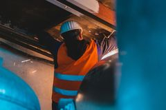 Industrial hvac repair installation worker process. Young man in orange work vest, safety belt and hard hat going to repair HVAC system. Toned photography stock image