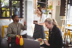 Young man ordering food to waitress while sitting with female friend Royalty Free Stock Photos