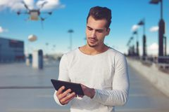 Young man ordering goods by drone, air delivery Stock Image