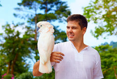 Young man, ornithologist holding gorgeous cockatoo parrot Stock Image