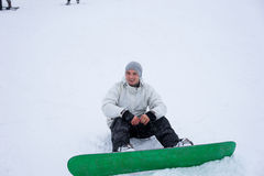 Young man out snowboarding sitting in snow Royalty Free Stock Image