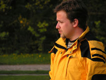 Young man outdoor. Young man with yellow jacket in a park looking sideways Stock Photography