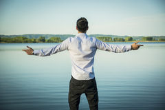 Young man outdoor with arms spread open enjoying. Young man in shirt, outdoor with arms spread open enjoying freedom in front of lake, seen from the back Royalty Free Stock Image