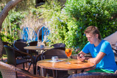 Young man in outdoor cafe talking on phone Stock Photography