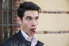 Young man outdoor doing silly face and stupid. Expression, looking to a side, crossed eyes royalty free stock images