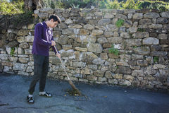 Young man outdoor sweeping foliage with broom Stock Image