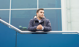 Young man outdoors. Casula young man on terrace looking to side. Gorgeous turk man in warmly jacket, outdoors - outside royalty free stock photo
