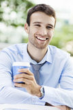 Young man outdoors with coffee Stock Images
