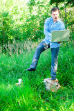 Acrobatic Young man outdoors with a cup and laptop Stock Image