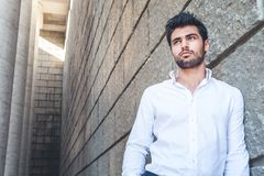 Young man outdoors with free space near. White shirt, fashionable hair and beard. royalty free stock photos