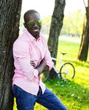 Young man outdoors. Young happy smiling african american wearing sunglasses with bicycle behind him in a park Royalty Free Stock Photo