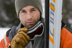 Young man outdoors, holding ski goggles and skis, portrait, close-up Stock Photo