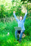 Young man outdoors with a cup and laptop Royalty Free Stock Image