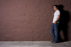 Young Man Outdoors at Night. Young white male standing outside at night near a wall Royalty Free Stock Photos