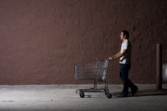 Young Man Outdoors at Night. Young white male with a shopping cart Stock Photography