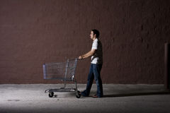 Young Man Outdoors at Night. Yount white male with a shopping cart Royalty Free Stock Images