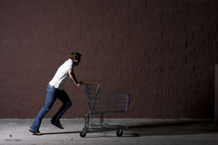 Young Man Outdoors at Night. Young white male with a shopping cart Royalty Free Stock Photography