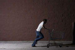 Young Man Outdoors at Night. Young white male with a shopping cart Royalty Free Stock Image