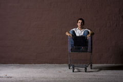 Young Man Outdoors at Night. Yount white male with a shopping cart Stock Photo