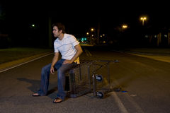 Young Man Outdoors at Night. Young white male outside at night with a shopping cart Royalty Free Stock Images