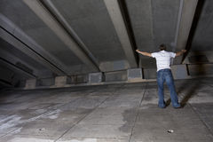Young Man Outdoors at Night. Young white male under an overpass at night with his arms raised Stock Images