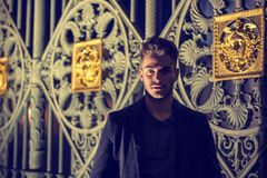 Young man outdoors at night, old elegant gate behind Stock Image