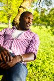 Young man outdoors. Young smiling african american lying on a tree branch in a park Stock Images