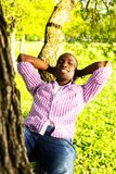 Young man outdoors. Young smiling african american lying on a tree branch in a park Royalty Free Stock Photo