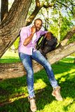 Young man outdoors. Young smiling african american sitting on a tree in park and calling with mobile phone Royalty Free Stock Photo