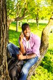 Young man outdoors. Young smiling african american sitting on a tree in park and calling with mobile phone Royalty Free Stock Photography