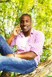 Young man outdoors. Young smiling african american sitting on a tree in park and calling with mobile phone Stock Image
