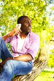 Young man outdoors. Young smiling african american sitting on a tree in park and calling with mobile phone Stock Photos