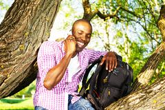 Young man outdoors. Young smiling african american sitting on a tree in park and calling with mobile phone Royalty Free Stock Image