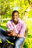 Young man outdoors. Young smiling african american sitting on a tree in park  with mobile phone Stock Photography