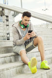 Young man outdoors texting and looking worried Stock Images
