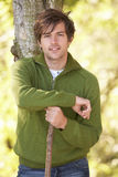Young Man Outdoors Walking In Autumn Woodland. Holding Walking Stick stock images