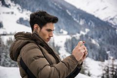 Young man in outerwear taking photo of landscape Stock Photography
