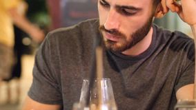 Young man outside at night using phone. Young handsome man outside at night sitting at bar table in a summer day in city, looking at smartphone stock video