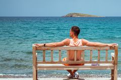Young man with outstretched arms, sitting on a wooden bench on the shore of the Mediterranean sea on the island of Crete and looki. Ng into the horizon Stock Photos