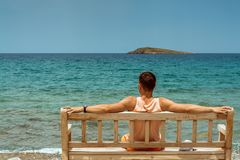 Young man with outstretched arms, sitting on a wooden bench on the shore of the Mediterranean sea on the island of Crete and looki. Ng into the horizon Stock Images