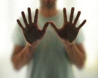 Young man with outstretched hands behind the glass Royalty Free Stock Photos