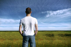 Young man overlooking farmland. Stock Photography