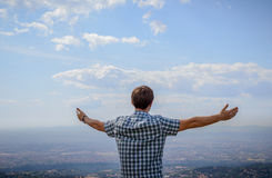 A young man overlooking the landscape from the hill with his arm Royalty Free Stock Image