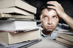 Young Man Overwhelmed and frustrated in education stress concept. Young student Man in stress Overwhelmed , overworked and frustrated among a pile of books and Royalty Free Stock Image