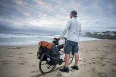 Young man with packed bicycle on beach Royalty Free Stock Photos