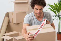 Young Man Packing Cardboard Box. Portrait Of A Young Man Packing Cardboard Box With Fragile Sellotape Royalty Free Stock Photography