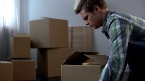 Young man packing things in cardboard boxes, moving from dormitory to own house. Stock photo royalty free stock photo