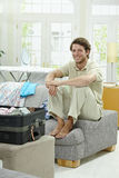 Young man packing for vacation Stock Photos
