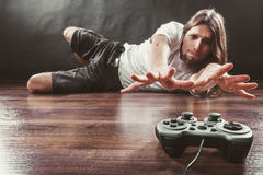 Young man with pad. Addiction and dependency concept. Young man with pad joystick playing games. Male addicted to console playstation videogames Stock Photos