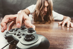 Young man with pad. Addiction and dependency concept. Young man with pad joystick playing games. Male addicted to console playstation videogames Royalty Free Stock Photo